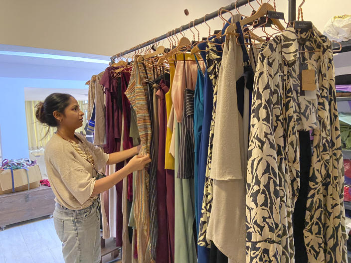 """Designer Suman Bhat browses through a display of her collections at Panjim in Goa, India, Dec.24, 2020. Sitting at home last summer during the lockdown, Bhat, whose luxury label """"Lola by SumanB'' with its flowing drape silhouettes is popular among Bollywood celebrities, struggled over whether to shut down her flagship brand store in Goa's capital Panjim or wait out the slump in sales. Bhat managed to retain her workers but had to give up her beloved retail space, moving to a less costly location in August. Bhat says her workers are exhausted by the new routines of sanitizing, testing and worry. With the pandemic's end still not in sight, the future remains uncertain. (AP Photo/Vineeta Deepak)"""