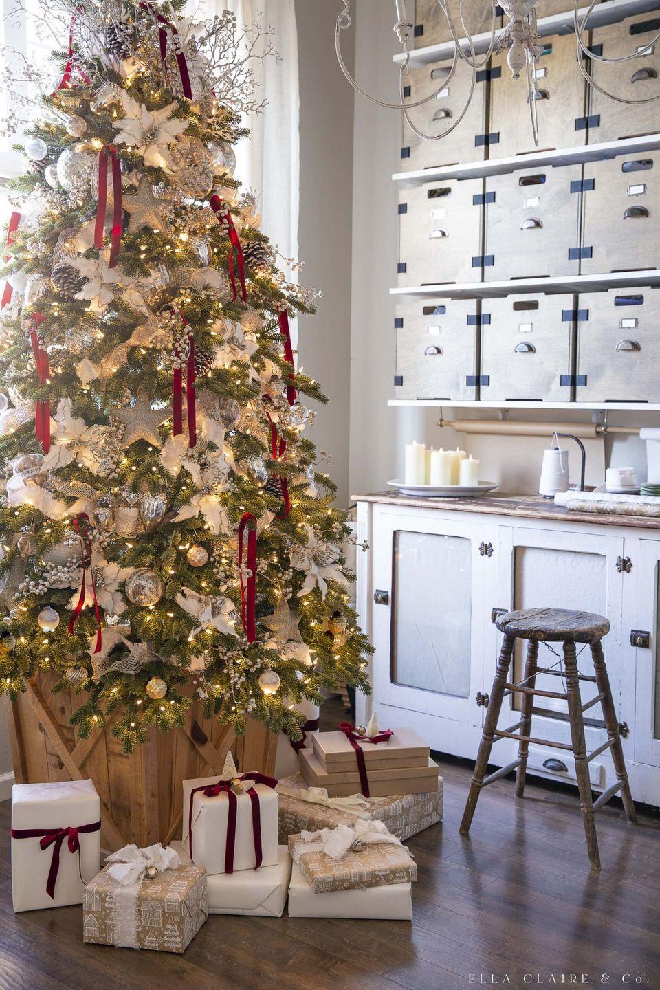 """<p>Keep things traditional with your tree this Christmas season with a red and gold tree that has cream-colored poinsettias, ribbon, and mercury glass accents. </p><p><strong><em>Get the tutorial at <a href=""""https://www.ellaclaireinspired.com/red-and-gold-christmas-tree/"""" rel=""""nofollow noopener"""" target=""""_blank"""" data-ylk=""""slk:Ella Claire & Co"""" class=""""link rapid-noclick-resp"""">Ella Claire & Co</a>.</em></strong></p><p><a class=""""link rapid-noclick-resp"""" href=""""https://www.amazon.com/OurWarm-Poinsettia-Christmas-Artificial-Decorations/dp/B076PDWZWN/?tag=syn-yahoo-20&ascsubtag=%5Bartid%7C10070.g.2025%5Bsrc%7Cyahoo-us"""" rel=""""nofollow noopener"""" target=""""_blank"""" data-ylk=""""slk:BUY CREAM POINSETTIAS"""">BUY CREAM POINSETTIAS</a><br></p>"""