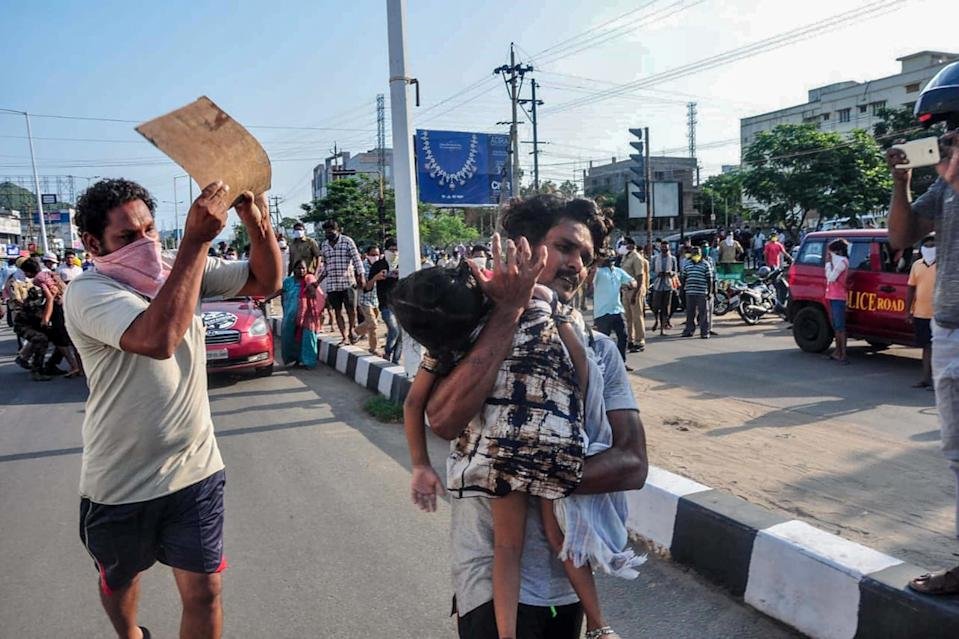 A man carries a young girl to evacuate her following a gas leak incident at an LG Polymers plant in Visakhapatnam on May 7, 2020.