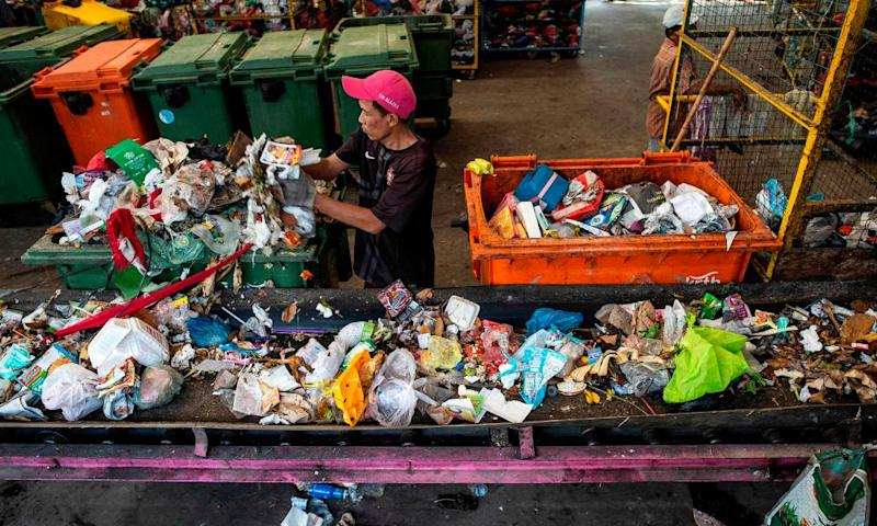 A worker gathers plastic waste at a trash bank in Surabaya, Indonesia's second largest city.