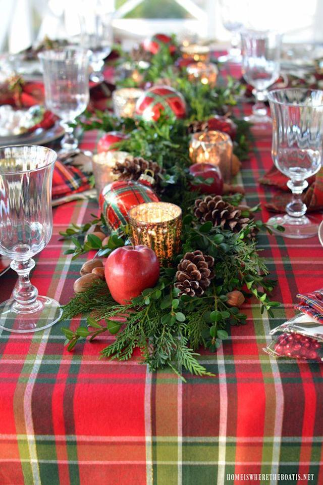 """<p>Leyland cypress, mercury glass votives, and pinecones lend a rustic yet festive air to this Christmas table. </p><p><strong>Get the tutorial at <a href=""""https://homeiswheretheboatis.net/2016/11/28/plaid-tidings-christmas-table-with-st-nick-and-a-natural-evergreen-table-runner/"""" rel=""""nofollow noopener"""" target=""""_blank"""" data-ylk=""""slk:Home Is Where the Boat Is"""" class=""""link rapid-noclick-resp"""">Home Is Where the Boat Is</a>.</strong></p><p><a class=""""link rapid-noclick-resp"""" href=""""https://www.amazon.com/s/ref=nb_sb_noss?url=search-alias%3Daps&field-keywords=plaid+ball+ornaments&rh=i%3Aaps%2Ck%3Aplaid+ball+ornaments&tag=syn-yahoo-20&ascsubtag=%5Bartid%7C10050.g.644%5Bsrc%7Cyahoo-us"""" rel=""""nofollow noopener"""" target=""""_blank"""" data-ylk=""""slk:SHOP ORNAMENTS"""">SHOP ORNAMENTS</a></p>"""