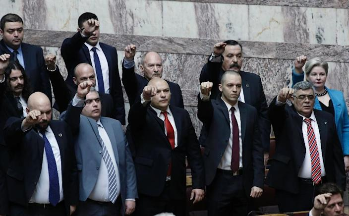 Leader of the far-right Golden Dawn party Nikolaos Michaloliakos (first row, R) and other members during a swearing-in ceremony on February 5, 2015 in Athens (AFP Photo/Yannis Kolesidis)