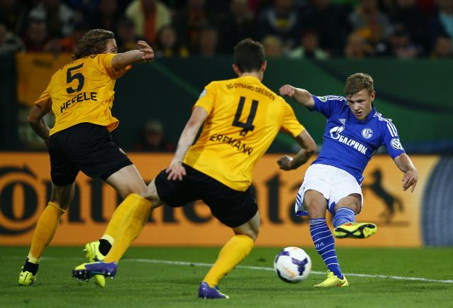 Dynamo Dresden's Michael Hefele (L) and Dennis Erdmann (2nd L) defend against Schalke 04's Max Meyer during their German soccer cup (DFB Pokal) match in Dresden August 18, 2014. REUTERS/Thomas Peter (GERMANY - Tags: SPORT SOCCER) DFB RULES PROHIBIT USE IN MMS SERVICES VIA HANDHELD DEVICES UNTIL TWO HOURS AFTER A MATCH AND ANY USAGE ON INTERNET OR ONLINE MEDIA SIMULATING VIDEO FOOTAGE DURING THE MATCH