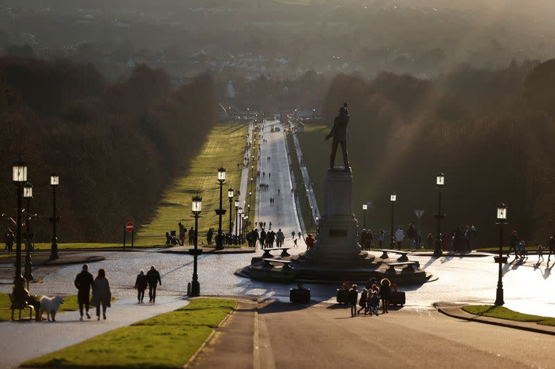 People walk through the grounds of the Stormont Parliament buildings in Belfast