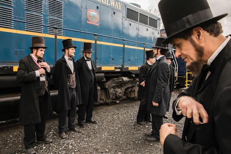 For 25 years, Abraham Lincoln lookalikes have met for the annual Association of Lincoln Presenters Conference. This year, the group traveled to Blue Ridge to take the scenic historic train ride to McCaysville for lunch and shopping. Here, a group of Lincolns hang out in front of the train before departing, on April 12. | Benjamin Norman for TIME