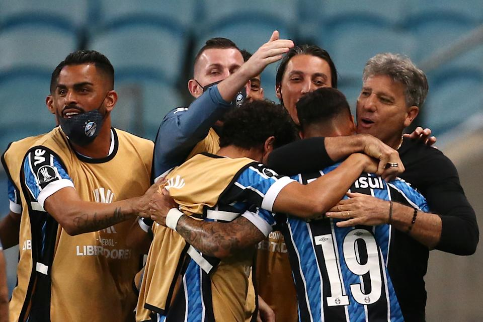 PORTO ALEGRE, BRAZIL - DECEMBER 03: Ferreira of Gremio celebrates with his coach Renato Portaluppi and teammates after scoring the first goal of his team during a round of sixteen second leg match of Copa CONMEBOL Libertadores between Gremio and Guarani at Arena do Gremio on December 03, 2020 in Porto Alegre, Brazil. (Photo by Diego Vara - Pool/Getty Images)