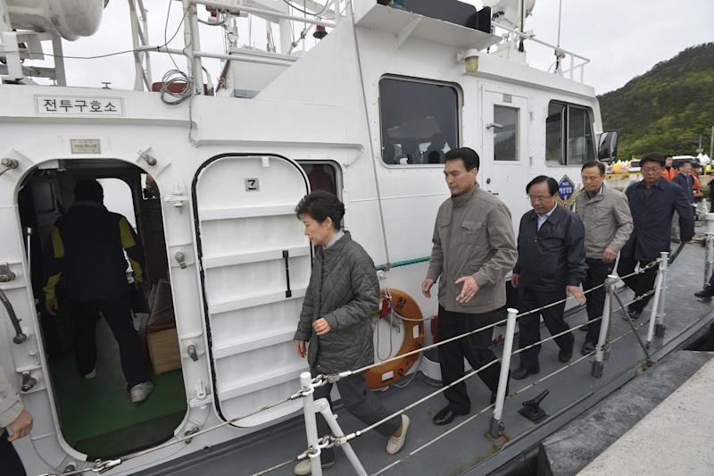South Korean President Park Geun-hye, left, boards a coast guard vessel at a port of Jindo, South Korea, to head to the site where the ferry Sewol sank in waters off the southern coast, Sunday, May 4, 2014. Park told families of those missing in the sunken ferry that her heart breaks knowing what they are going through, as divers recovered two more bodies on Sunday. (AP Photo/Yonhap) KOREA OUT