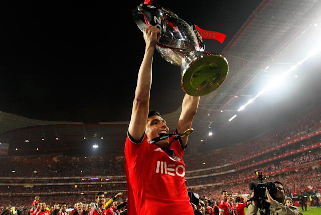 Benfica's Oscar Cardozo, from Paraguay, lifts the trophy celebrating at the end of their Portuguese league soccer match with Olhanense on Sunday April 20, 2014, at Benfica's Luz stadium in Lisbon. Benfica defeated Olhanense 2-0 to win the championship with two rounds left to play. (AP Photo/Francisco Seco)