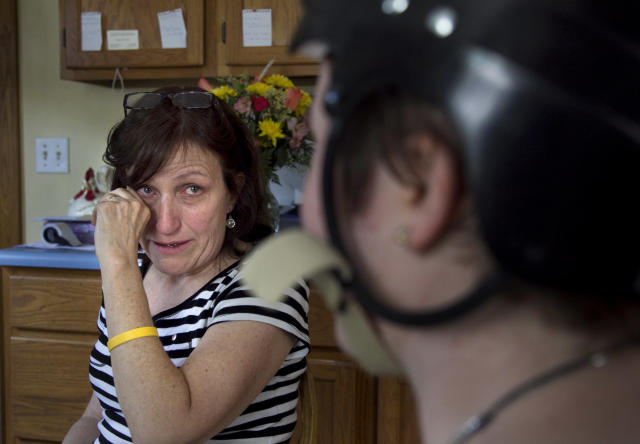 In this Thursday, Aug. 2, 2012 photo, Deb Theriault, left, wipes a tear from her eye from joy that her daughter Meg Theriault, right, survived an accident in New Zealand two-and-a-half months earlier, while reflecting on her daughter's homecoming in Salisbury, Mass. Three Boston University students were killed in the crash when the minivan they were traveling in flipped over during a trip in New Zealand while they were studying abroad. (AP Photo/Steven Senne)