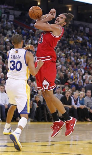 Chicago Bulls' Joakim Noah (13) has the ball stripped by Golden State Warriors' Stephen Curry (30) during the first half of an NBA basketball game Monday, Dec. 26, 2011, in Oakland, Calif. (AP Photo/Tony Avelar)