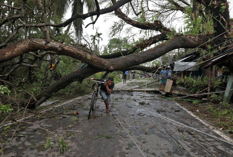 A man walks with his bicycle under an uprooted tree after Cyclone Amphan made its landfall, in South 24 Parganas district