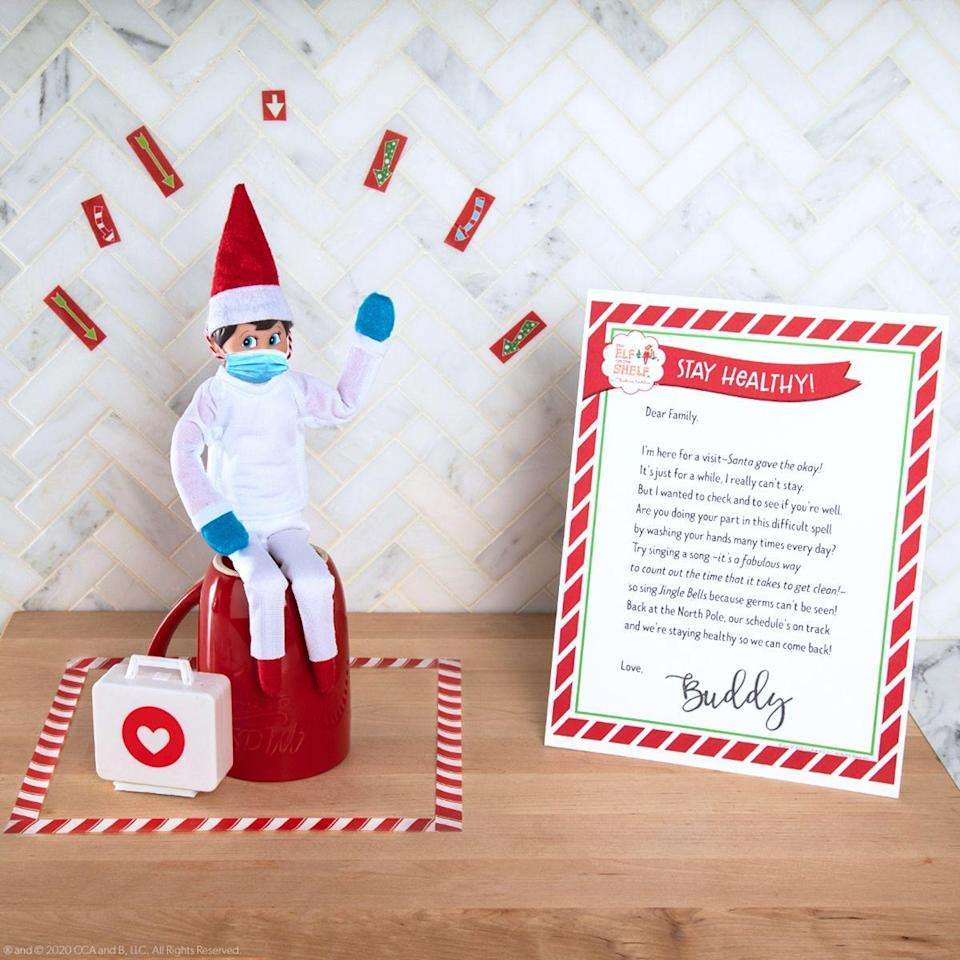 """<p>It's 2020, so of course your elf needs his own face mask. Pose him next to a letter (<a href=""""https://media.elfontheshelf.com/files/managed/2020-04-23-2-quarantine-letter.pdf"""" rel=""""nofollow noopener"""" target=""""_blank"""" data-ylk=""""slk:download it for free here"""" class=""""link rapid-noclick-resp"""">download it for free here</a>) reminding your kids to wash their hands. </p>"""
