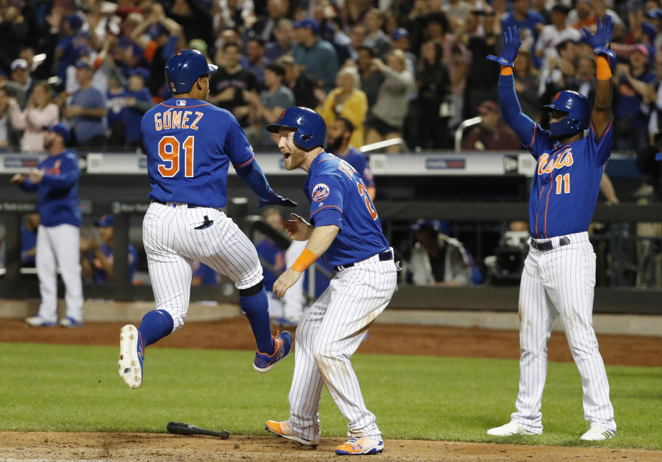 New York Mets' Carlos Gomez (91) leaps as he scores on Juan Lagares's eighth-inning, three-run double in a baseball game against the Washington Nationals, Wednesday, May 22, 2019, in New York. Todd Frazier (21) and Adeiny Hechavarria (11) greet Gomez after they scored. (AP Photo/Kathy Willens)