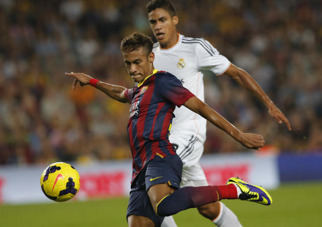 Barcelona's Neymar, centre, challenges for the ball with Real Madrid's Raphael Varane during a Spanish La Liga soccer match between Barcelona F.C. and Real Madrid at the Camp Nou stadium in Barcelona, Spain, Saturday, Oct. 26, 2013. (AP Photo/Emilio Morenatti)