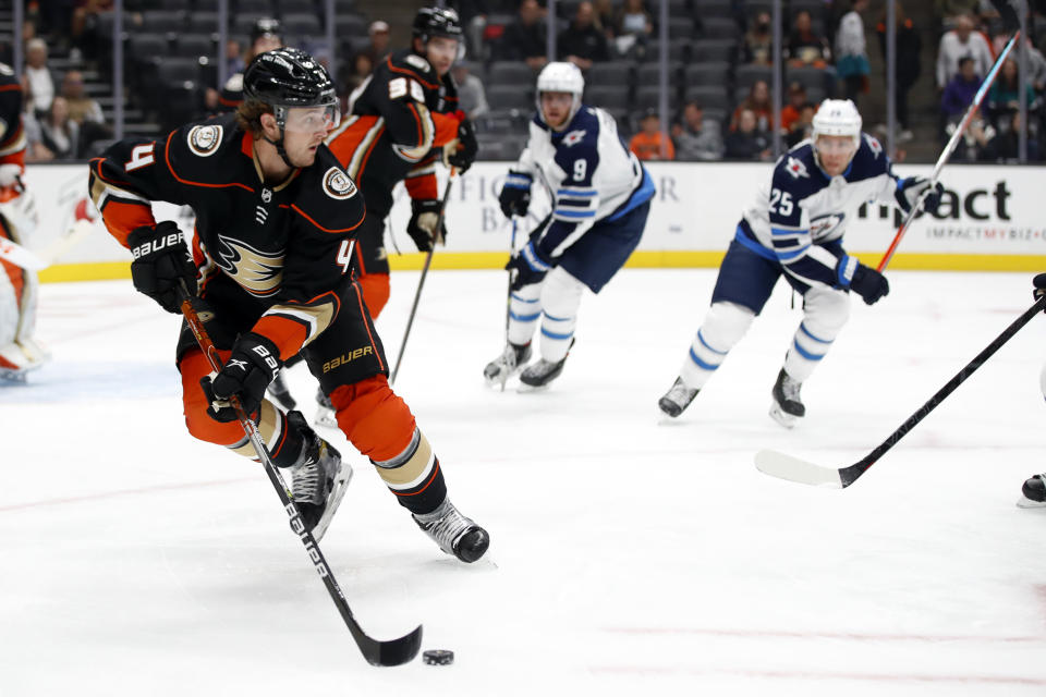 Anaheim Ducks defenseman Cam Fowler, left, controls the puck away from Winnipeg Jets centers Andrew Copp (9) and Paul Stastny (25) during the first period of an NHL hockey game in Anaheim, Calif., Wednesday, Oct. 13, 2021. (AP Photo/Alex Gallardo)
