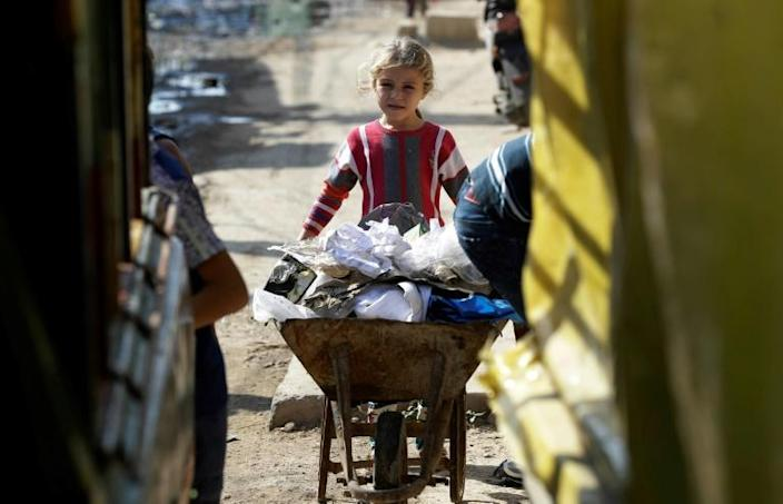 A Lebanese girl pushes a cart full of garbage at an empoverished neighbourhood in the port city of Tripoli (AFP Photo/JOSEPH EID)
