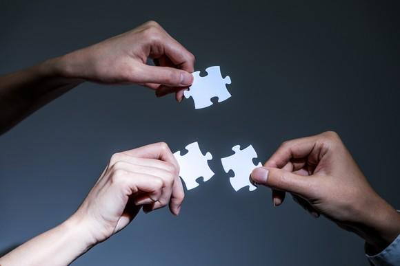 Three hands holding jigsaw puzzle pieces