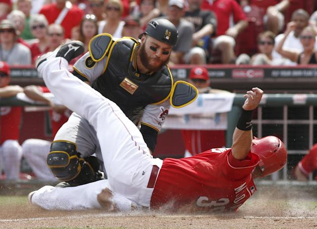 Cincinnati Reds' Devin Mesoraco, right, is tagged out at home by Pittsburgh Pirates catcher Russell Martin during the sixth inning of a baseball game, Sunday, July 13, 2014, in Cincinnati. (AP Photo/David Kohl)