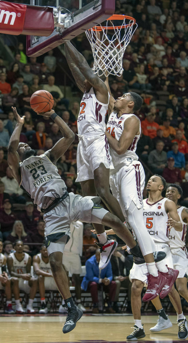 Wake Forest guard Chaundee Brown (23) shoots the ball against Virginia Tech guard Ty Outlaw (42) and Virginia Tech forward Kerry Blackshear Jr. (24) during the first half of an NCAA college basketball game Saturday, Jan. 19, 2019, in Blacksburg, Va. (AP Photo/Don Petersen)