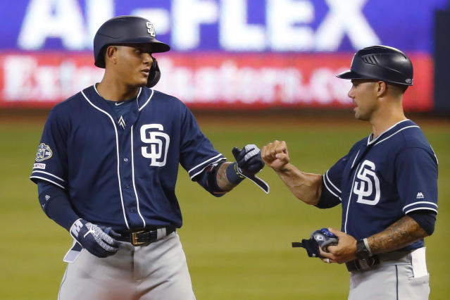 San Diego Padres' Manny Machado, left, is congratulated by third base coach Glenn Hoffman after getting a base hit during the first inning of the team's baseball game against the Miami Marlins, Wednesday, July 17, 2019, in Miami. (AP Photo/Wilfredo Lee)