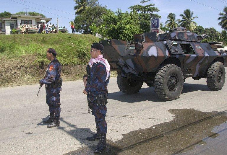 Policemen are pictured standing guard in Davao, southern Philippines, on April 3, 2003