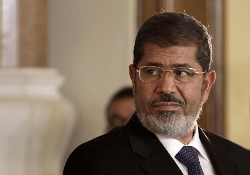 FILE - In this Friday, July 13, 2012 file photo, Egyptian President Mohammed Morsi holds a joint news conference with Tunisian President Moncef Marzouki at the Presidential palace in Cairo, Egypt. Egyptian authorities switched the venue for the trial of the former Islamist president on Sunday, Nov. 3, 2013 a last-minute change made after the Muslim Brotherhood called for mass demonstrations at the original location. The trial of Morsi, now to be held east of the capital on Monday, could lead to another round of bloodshed as his supporters look likely to face an emboldened security apparatus that has boosted its forces for the hearing. (AP Photo/Maya Alleruzzo, File)