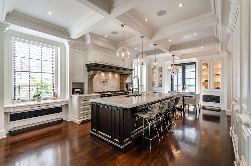 The kitchen features a grand centre island in marble. There's a <em>Lacanche Cote d'Or</em> 9-burner gas stove with double ovens, large Miele refrigerator, large Miele freezer, Miele dishwasher, compactor, double sink, garburator and pot filler.