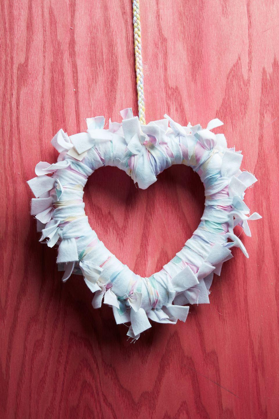 """<p>Wrap strips of soft flannel around a heart-shaped foam wreath form to create a soft statement piece that says """"I love you!""""<br><br><a class=""""link rapid-noclick-resp"""" href=""""https://www.amazon.com/Decorate-Garland-Valentines-Decoration-Rely2016/dp/B0799MLQTQ/ref=sr_1_9?tag=syn-yahoo-20&ascsubtag=%5Bartid%7C10050.g.35057743%5Bsrc%7Cyahoo-us"""" rel=""""nofollow noopener"""" target=""""_blank"""" data-ylk=""""slk:SHOP WREATH FORM"""">SHOP WREATH FORM</a></p>"""