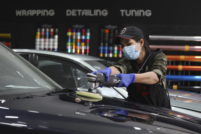 Iranian car detailer Maryam Roohani polishes a car at a detailing shop in Tehran, Iran, April 18, 2021. Roohani has battled skeptics and stereotypes to live out her dream of working as a professional detailer. The auto industry remains male-dominated around the world, let alone in the tradition-bound Islamic Republic. Still Iranian women, especially in the cities, have made inroads over the years. (AP Photo/Vahid Salemi)