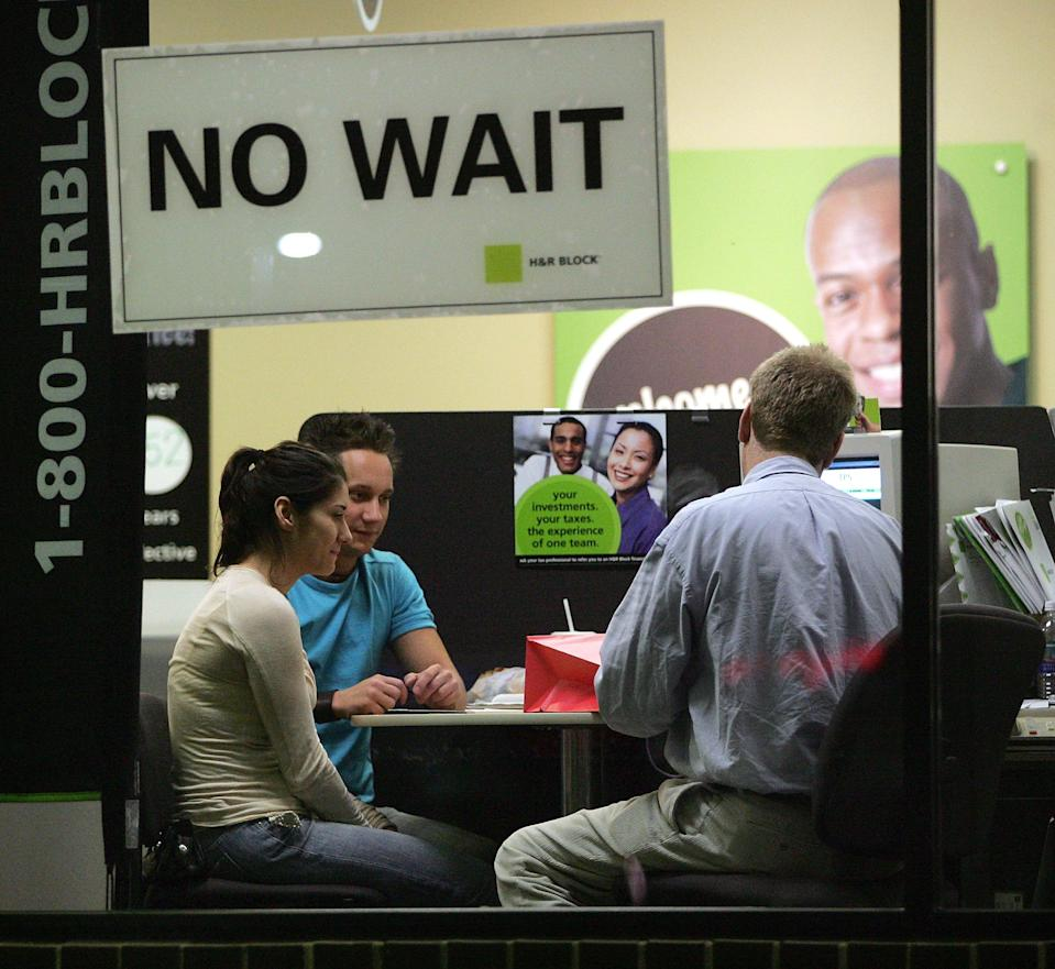 Visible through a window, an H&R Block tax preparer (R) assists Senada Imsirovic (L) sitting next to her friend Kevin Schwaner, with her taxes. (Photo: Tim Boyle/Getty Images)