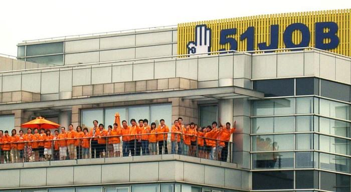 51job employees in orange shirts, on the patio outside of 51job headquarters in China.