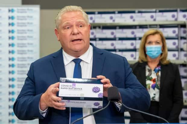 Ontario Premier Doug Ford holds up COVID-19 rapid testing device at Humber River Hospital in November.