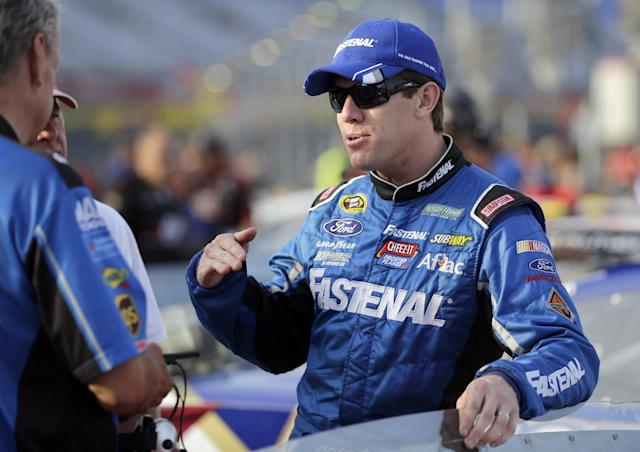 Carl Edwards talks with crew members before qualifying for Sunday's NASCAR Sprint Cup series auto race at Charlotte Motor Speedway in Concord, N.C., Thursday, May 22, 2014. (AP Photo/Chuck Burton)
