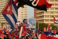 People carry a poster with photographs of Fidel Castro, Miguel Diaz-Canel and Raul Castro during a rally in Havana