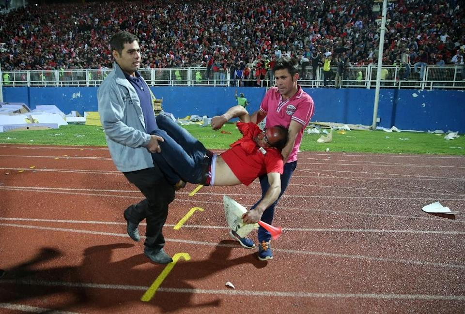 An injured Tractor Sazi fan is carried off the pitch on May 15, 2015 (AFP Photo/Omid Vahabzadeh)