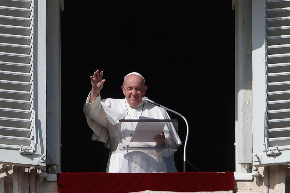 Pope Francis waves at the end of his Angelus noon prayer Sunday from the window of his studio overlooking St. Peter's Square at the Vatican.