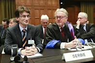 Members of the Serbian delegation, First Counsellor Sasa Obradovic, left, William Schabas, center and Andreas Zimmermann, right, await the start of public hearings at the International Court of Justice (ICJ) in The Hague, Netherlands, Monday, March 3, 2014. Croatia is accusing Serbia of genocide during fighting in the early 1990's as the former Yugoslavia shattered in spasms of ethnic violence, in a case at the United Nations' highest court that highlights lingering animosity in the region. Croatia is asking the ICJ to declare that Serbia breached the 1948 Genocide Convention when forces from the former Federal Republic of Yugoslavia attempted to drive Croats out of large swaths of the country after Zagreb declared independence in 1991. (AP Photo/Jiri Buller)