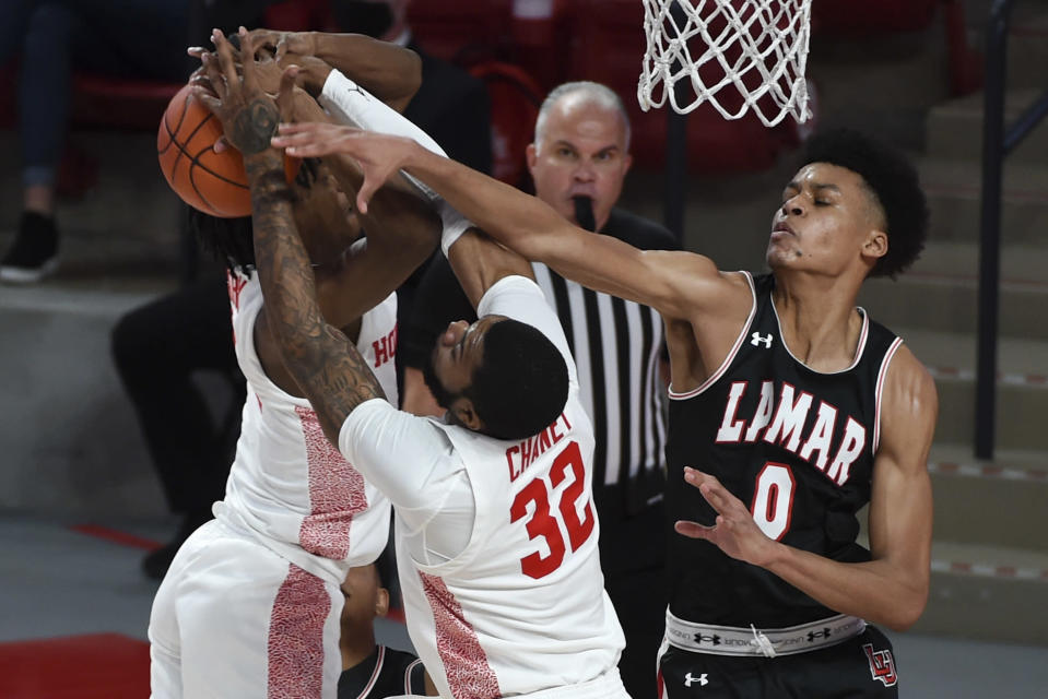 Lamar center David Muoka (0), Houston forward Reggie Chaney (32), and guard Tramon Mark, left, vie for a rebound during the first half of an NCAA college basketball game, Wednesday, Nov. 25, 2020, in Houston. (AP Photo/Eric Christian Smith)