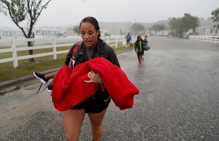 During a driving rain, Maggie Belgie of The Cajun Navy, carries a child evacuating a flooding trailer community during Hurricane Florence in Lumberton, North Carolina, U.S. September 15, 2018.  REUTERS/Randall Hill