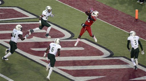 Louisville's Eli Rogers makes a catch in the middle of South Florida defenders clockwise from bottom left, JaQuez Jenkins, Kayvon Webster, DeDe Lattimore, and Mark Joyce, to put Louisville up 27-25 during their NCAA college football game Saturday Oct. 20, 2012 in Louisville, Ky. (AP Photo/ Timothy D. Easley)