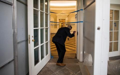 A Secret Service agent checks on the Oval Office of the White House in Washington, Friday, Aug. 11, 2017, as the West Wing of the White House in Washington is undergoing renovations while President Donald Trump is spending time at his golf resort in New Jersey - Credit: AP