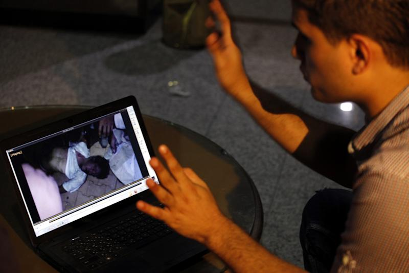Fahd al-Bakoush, a freelance videographer, 22, shows a video he took of the body of U.S. Ambassador Chris Stevens being carried out of a small dark room in the U.S. consulate in Benghazi, during an interview with the Associated Press, in Benghazi, Libya, Monday, Sept. 17, 2012. The video has been authenticated since Stevens' face is clearly visible and he is wearing the same white t-shirt seen in authenticated photos of him being carried away on another man's shoulders, presumably moments later. Stevens and three other Americans were killed in the attack on the consulate on the night of Tuesday, September 11, 2012, as part of a wave of assaults on U.S. diplomatic missions in Muslim countries over a low-budget movie made in the United States that denigrates the Prophet Muhammad. (AP Photo/Mohammad Hannon)