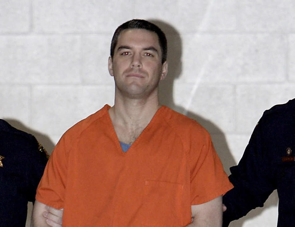 FILE - In this March 17, 2005, file photo, Scott Peterson is escorted by two San Mateo County Sheriff deputies to a waiting van in Redwood City, Calif. California prosecutors said Tuesday, June 1, 2021, that they won't again seek the death penalty against Peterson in the 2002 slaying of his pregnant wife even if he is granted a new trial based on juror misconduct. (Justin Sullivan/Pool Photo via AP, File)