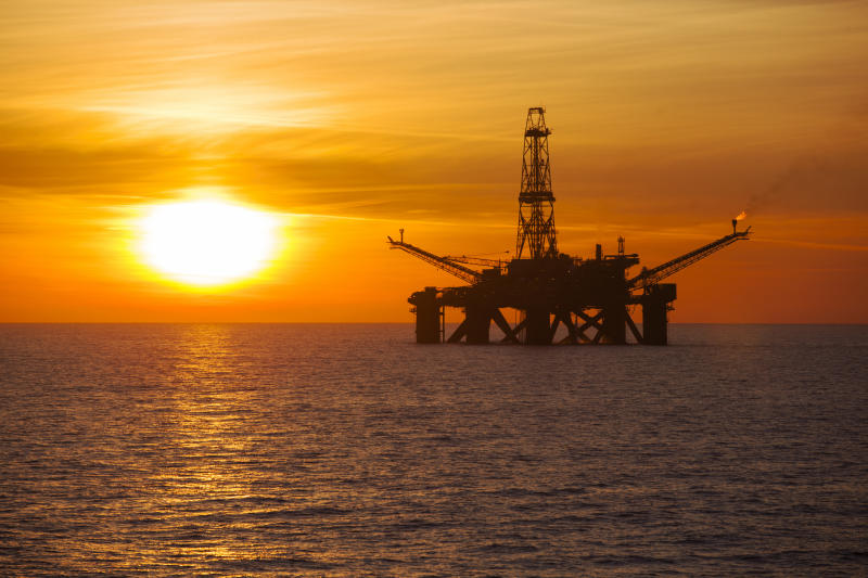 An offshore oil rig at sunset.
