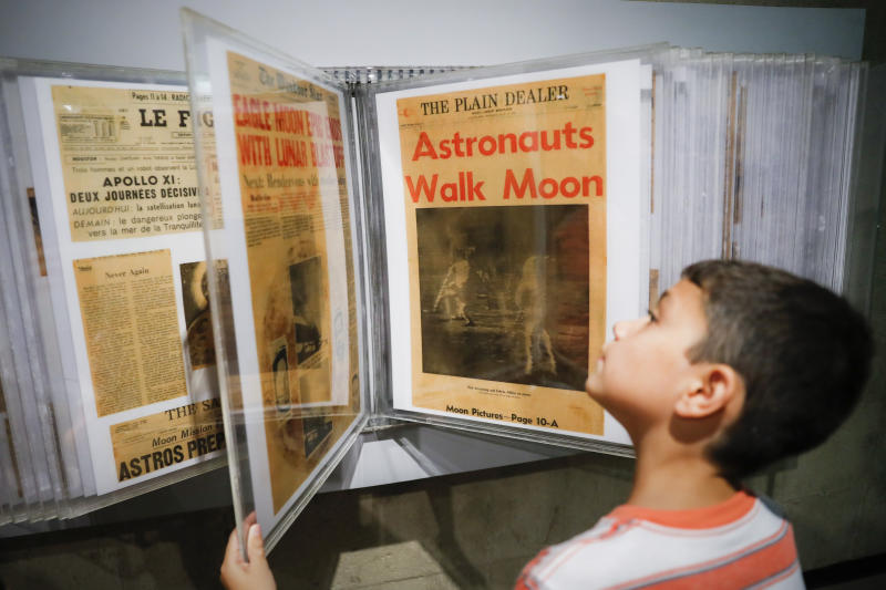 Ethan Reynolds browses a display of archival newspaper front pages announcing the first moon landing at the Armstrong Air and Space Museum as special events are underway for visitors commemorating the milestone's 50th anniversary, Saturday, July 20, 2019, in Wapakoneta, Ohio. (AP Photo/John Minchillo)