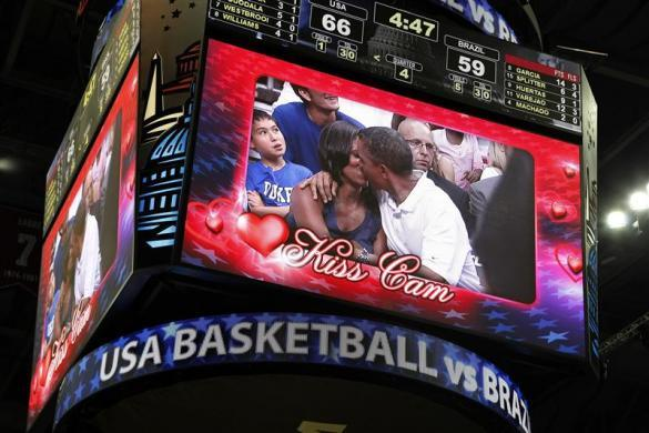 "Barack Obama and first lady Michelle Obama are shown kissing on the ""Kiss Cam"" screen during a timeout in the Olympic basketball exhibition game between the U.S. and Brazil national men's teams in Washington, July 16, 2012."