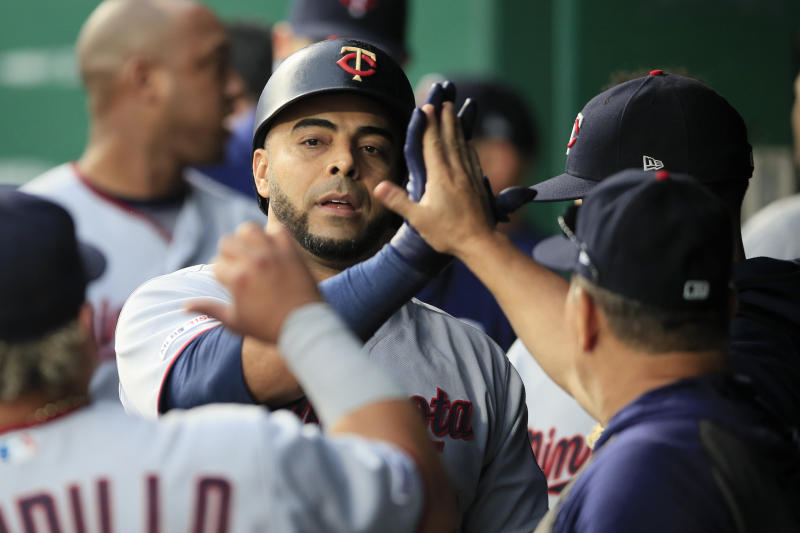 Minnesota Twins designated hitter Nelson Cruz is congratulated by teammates after his solo home run in the eighth inning of a baseball game against the Kansas City Royals at Kauffman Stadium in Kansas City, Mo., Saturday, Sept. 28, 2019. (AP Photo/Orlin Wagner)