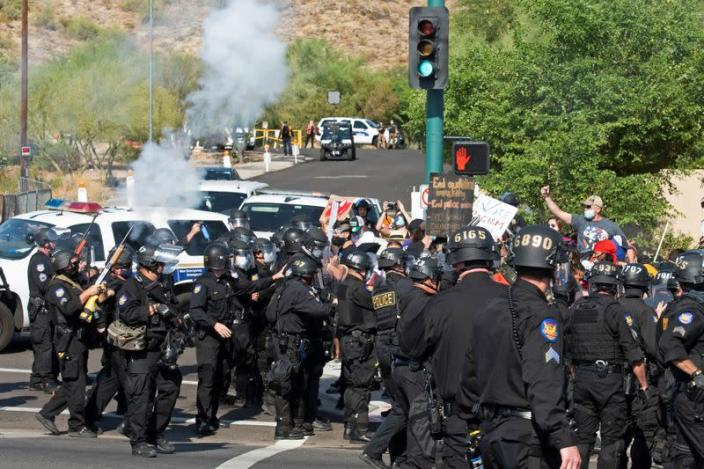 Police fire crowd control weapons during the visit by U.S. President Donald Trump to the Dream City Church in Phoenix