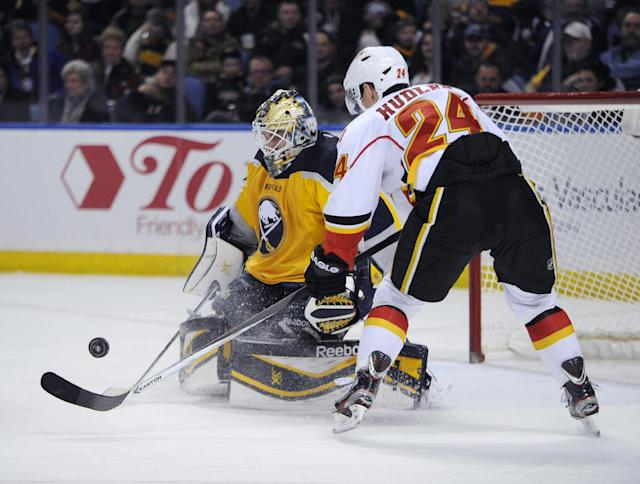 Buffalo Sabres goaltender Jhonas Enroth (1), of Sweden, makes a save as Calgary Flames Jiri Hudler (24), of the Czech Republic, chases the rebound during the second period of an NHL hockey game in Buffalo, N.Y., Saturday Dec. 14, 2013. (AP Photo/Gary Wiepert)