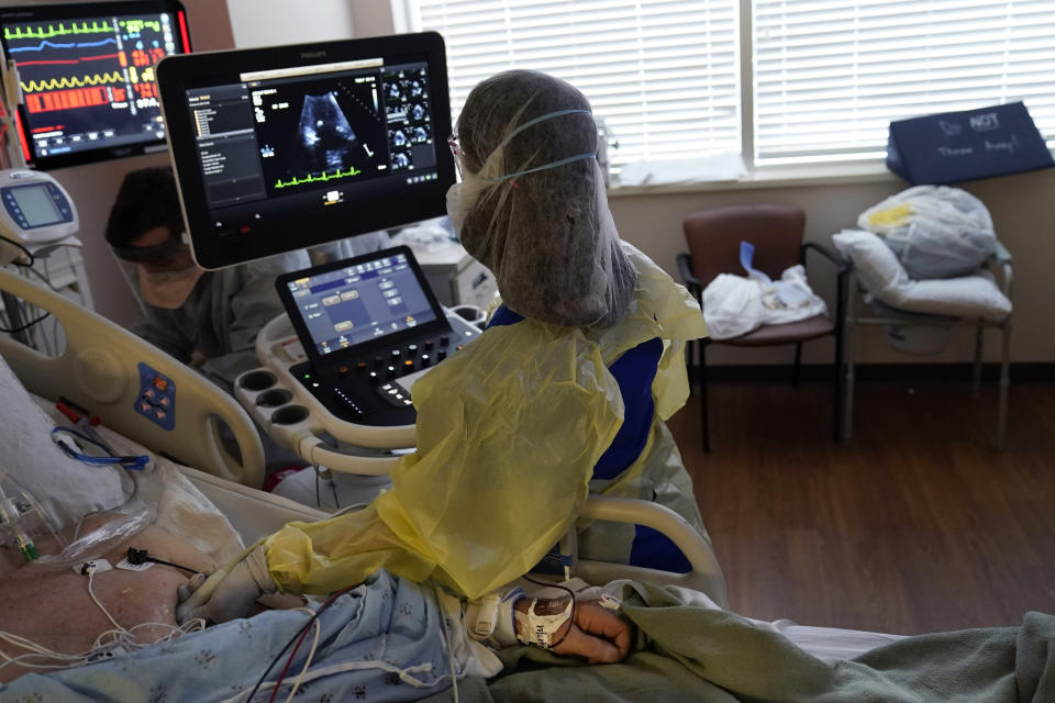 Tracy Brooks, an echocardiogram technician, takes readings from a critically ill COVID-19 patient, in an intensive care unit at the Willis-Knighton Medical Center in Shreveport, La., Tuesday, Aug. 17, 2021. The hospital in northwestern Louisiana thought the COVID-19 pandemic was letting up. Then came the ongoing surge caused by the delta variant. (AP Photo/Gerald Herbert)
